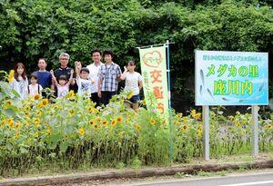 案内看板と植栽したヒマワリのそばに立つ会員と子どもたち