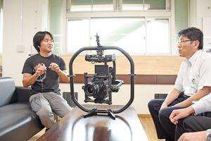 動画を制作した永川優樹さん(左)。中央は撮影で使用したシネマカメラ=佐賀市役所