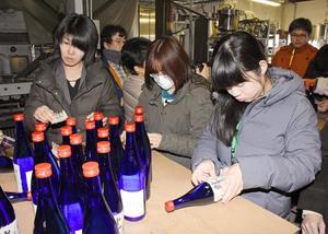 復興への思いを込め、一瓶ずつラベルを貼るユニカレさがの生徒たち=みやき町の天吹酒造
