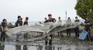 水位の下がった池で投網する学生=佐賀市の県立森林公園