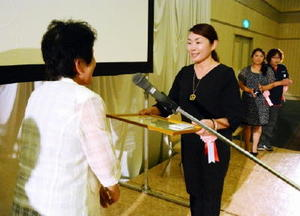 最優秀賞に輝き、賞状を受け取るJA白石地区女性部の森田良子さん(右)=佐賀市のマリトピア