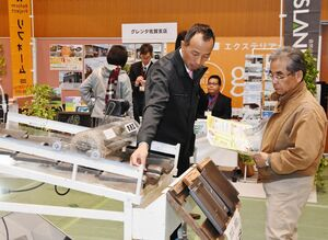 企業担当者から耐震や災害に強い設備の説明を受ける来場者(右)=佐賀市のメートプラザ佐賀