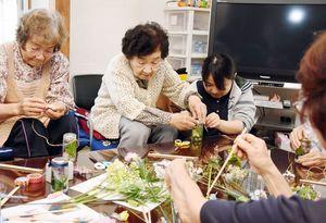 西九州大の学生(右)とハーバリウム作りを楽しむ利用者たち=吉野ヶ里町目達原の「すずめカフェ」
