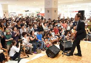 新曲「お義父さん」の発売前イベントで、大勢の観客の前で熱唱するはなわさん=佐賀市のイオン佐賀大和店