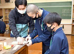 教諭に教わりながら、工具を使って木材を固定する生徒=嬉野市の嬉野中学校