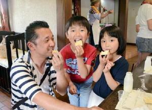 手作りのバターをクラッカーに塗り、仲良く頬張る親子=佐賀市三瀬村のどんぐり村