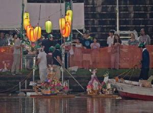 飾りつけた精霊船を送り出す遺族ら=佐賀市久保田町の嘉瀬川河川敷