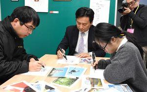 佐賀をイメージしたデザイン画を描く山口祥義知事ら=基山町の就労継続支援B型事業所「ピクファ」