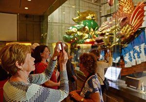 クルーズ船のツアーで、曳山展示場を訪れた外国人客。ガイドの説明を熱心に聞き、しきりにシャッターを切っていた=唐津市