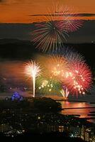 夕闇に包まれた唐津の街を色とりどりの花火が明るく染めた九州花火大会。左は唐津城=17日午後8時過ぎ、唐津市の鏡山長時間露光、撮影・山口源貴)