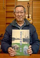 写真集「筑紫次郎物語-続編」を手にする本間雄治さん=佐賀市の自宅