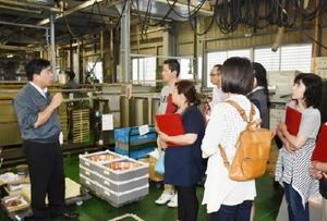 田口英信社長(左)から説明を受ける有田工高の保護者ら=基山町小倉の田口電機工業