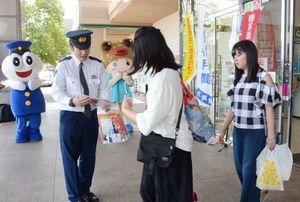 消費生活センターや警察関係者から啓発グッズを受け取る来場者=佐賀市のゆめタウン佐賀