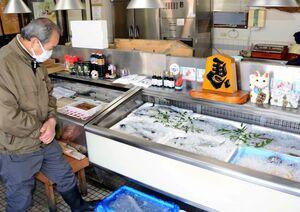 「1日も早く終息してほしい」と話す峰松喜照さん。新型コロナウイルスの感染拡大で学校給食停止だけでなく、宴会中止が相次ぐなどして鮮魚の発注が減少しているという=鹿島市内の鮮魚店