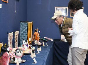 佐賀錦をまとった木目込み人形や名刺入れ、スマホケースなど50点を超える作品が並ぶ=佐賀市のNHK佐賀放送局ギャラリー