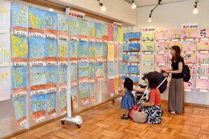 園児らが描いた菜の花の絵が展示されている=伊万里市民図書館