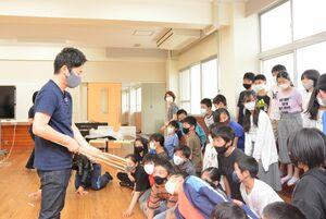 吉岡徳仁さんが持つトーチをのぞき込む児童=佐賀市の西与賀小