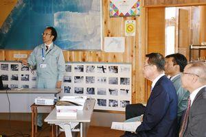 久野所長(左)から説明を受ける吉川農相(右から2人目)=小城市の有明水産振興センター
