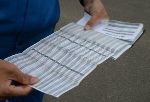 元山英信社長が常に携帯している手帳にはスケジュールの他、クレーンに関する資料などがびっしりと詰め込まれている=杵島郡大町町の同社