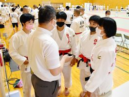 柔道女子団体で優勝し、監督のもとに集まる佐賀商の選手たち=基山町総合体育館
