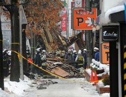 爆発のあった建物付近で、現場検証する警察官や消防隊員ら=17日午前、札幌市豊平区