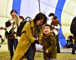 球皮内のひもを引っ張る子ども=佐賀市の嘉瀬川河川敷