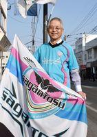 勝利を祈ってフラッグを掲げる伊藤龍雄さん。後方に鳥栖駅、その向こうにスタジアムがある=鳥栖市本通筋商店街