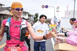 今大会から初めて給食に加わったカプリコを求めるランナー=佐賀市大和町の第13給水・給食所