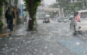 水しぶきを上げながら冠水した道路を通行する車=6日午後3時50分ごろ、佐賀市水ケ江