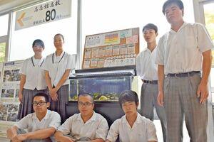 調査で見つけた絶滅危惧種などを展示する高志館高の環境クラブの部員たち=佐賀市の同校