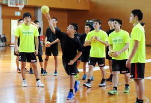 トヨタ紡織九州の選手たちにアドバイスを受けながらシュート練習に汗を流す熊本の中学生=熊本県熊本市の千原台高体育館