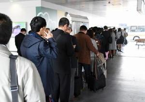 福岡市行きのバスを待つビジネスマンや旅行者ら=佐賀市の佐賀駅バスセンター