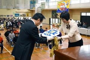 塚部芳和市長に校旗を返納する西山太佳子校長(右)。いずれも波多津小OBで塚部市長は「運命的な巡り合わせ」と語った=伊万里市波多津町の波多津小学校