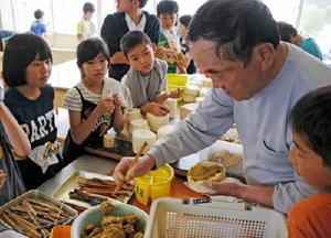 尾崎人形保存会の髙柳さんの手仕事に熱い視線を向ける子どもたち=神埼市の西郷小学校