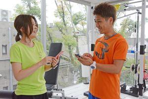 健康管理アプリを利用するトレーナー(右)と利用客=佐賀市のフィットネススタジオ「リリスタイル」
