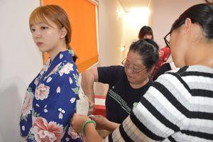 町民らに手伝ってもらい浴衣をまとう外国人女性=白石町「元気のたまご」