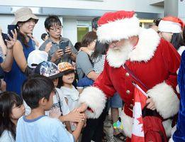 出迎えた子どもたちと握手を交わすサンタクロース=佐賀市川副町の佐賀空港