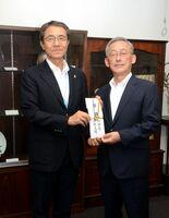 落合裕二教育長(左)に目録を手渡した大西久孝支部長=県庁