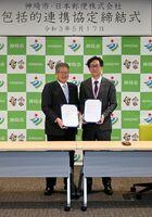 協定書に署名した脊振郵便局の廣瀧直義局長(右)と松本茂幸神埼市長=神埼市役所