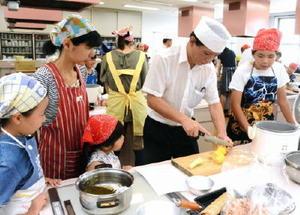 炊き込みごはんに使うトウモロコシの切り方を指導する和食の料理人=佐賀市のアバンセ