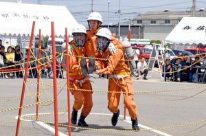 救助を求める人が地下にいる想定で、2人一組で抱えて救助する隊員たち=佐賀市の県消防学校
