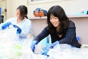 蒸し暑い中、ボランティア活動でペットボトルを分別する佐賀大学生の谷本有紀奈さん(右)=佐賀市の佐賀大学本庄キャンパス