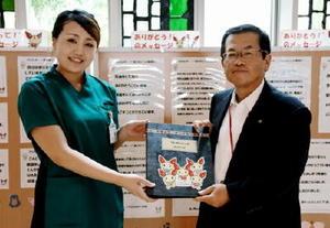 患者からのメッセージを好生館の本山千恵さんから受け取った県赤十字血液センターの松山博之所長(右)=佐賀市の県医療センター好生館
