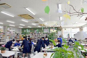 植物などで飾り付けられた図書館を利用する生徒=白石中