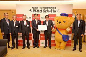 包括連携協定を結んだ佐賀県と日本郵便の関係者たち=県庁