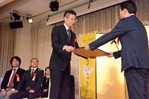 山口祥義知事から賞状を受け取るKMTecの久米社長(左)=佐賀市