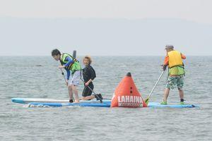 他の出場者と争いながらブイを回る藤本拓希記者(左)。方向転換でふらつき、腰が引けている=唐津市の浜崎海岸
