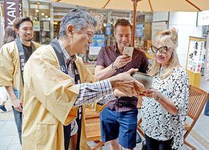 地元の観光協会から、地酒と唐津焼の器でもてなしを受けるクルーズ船の外国人客=唐津市呉服町