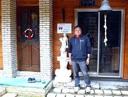 多くの人が協力して建設した手作りホールの玄関に立つ代表の船津静哉さん=多久市多久町