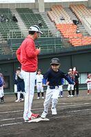 緒方孝市さん(左)の指導を受け、ベースの角を踏むよう意識して走る参加者=佐賀市のみどりの森県営球場